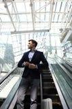 Επιχειρηματίας στον αερολιμένα που πηγαίνει κάτω από την κυλιόμενη σκάλα Στοκ φωτογραφία με δικαίωμα ελεύθερης χρήσης