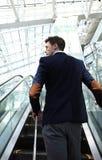 Επιχειρηματίας στον αερολιμένα που πηγαίνει κάτω από την κυλιόμενη σκάλα Στοκ Φωτογραφίες