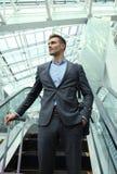 Επιχειρηματίας στον αερολιμένα που πηγαίνει κάτω από την κυλιόμενη σκάλα Στοκ εικόνες με δικαίωμα ελεύθερης χρήσης