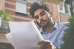 Επιχειρηματίας στον καφέ οδών που μιλά στο έξυπνα τηλέφωνο και το Πε στοκ εικόνα με δικαίωμα ελεύθερης χρήσης