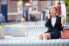 Επιχειρηματίας στον πάγκο πάρκων με τον καφέ που χρησιμοποιεί το κινητό τηλέφωνο Στοκ φωτογραφίες με δικαίωμα ελεύθερης χρήσης