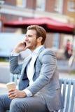 Επιχειρηματίας στον πάγκο πάρκων με τον καφέ που χρησιμοποιεί το κινητό τηλέφωνο Στοκ φωτογραφία με δικαίωμα ελεύθερης χρήσης