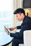 Επιχειρηματίας στο ασιατικό δωμάτιο ξενοδοχείου που λειτουργεί με την ταμπλέτα Στοκ φωτογραφίες με δικαίωμα ελεύθερης χρήσης