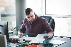 Επιχειρηματίας στο γραφείο, στο γράψιμο γραφείων του, που ελέγχει το ύφασμα στοκ εικόνες