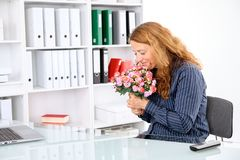 Επιχειρηματίας στο γραφείο με τη μεγάλη ανθοδέσμη των λουλουδιών στοκ εικόνες