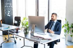 Επιχειρηματίας στο γραφείο με τον υπολογιστή στο γραφείο του Στοκ Εικόνες