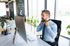 Επιχειρηματίας στο γραφείο με τον υπολογιστή στο γραφείο του Στοκ Φωτογραφίες