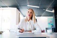 Επιχειρηματίας στο γραφείο με το σημειωματάριο στο γραφείο της Στοκ Εικόνες