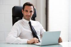 Επιχειρηματίας στο γραφείο με το φορητό προσωπικό υπολογιστή Στοκ εικόνα με δικαίωμα ελεύθερης χρήσης