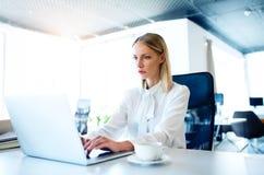 Επιχειρηματίας στο γραφείο με το lap-top στο γραφείο της Στοκ Εικόνες