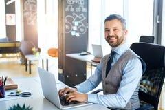 Επιχειρηματίας στο γραφείο με το lap-top στο γραφείο του Στοκ Φωτογραφία