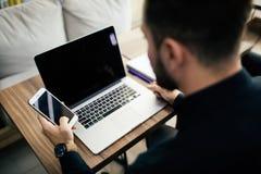 Επιχειρηματίας στο γραφείο με το lap-top χρησιμοποιώντας οικονομικό app στο έξυπνο τηλέφωνό του και εργαζόμενος στις εκθέσεις, χέ Στοκ φωτογραφία με δικαίωμα ελεύθερης χρήσης