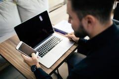 Επιχειρηματίας στο γραφείο με το lap-top χρησιμοποιώντας οικονομικό app στο έξυπνο τηλέφωνό του και εργαζόμενος στις εκθέσεις, χέ Στοκ Εικόνες
