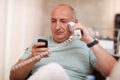 Επιχειρηματίας στο γραφείο που μιλά σε δύο τηλέφωνα Στοκ Εικόνα