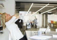 Επιχειρηματίας στο γραφείο που παίρνει ένα σπάσιμο και που κάνει έναν λαιμό exer Στοκ Εικόνες