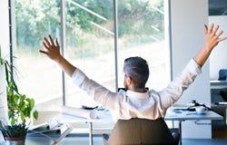 Επιχειρηματίας στο γραφείο στα όπλα τεντώματος γραφείων του Στοκ φωτογραφίες με δικαίωμα ελεύθερης χρήσης