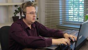 Επιχειρηματίας στο γραφείο στην εισαγωγή τηλεφώνων, κασκών και στοιχείων σε ένα lap-top απόθεμα βίντεο