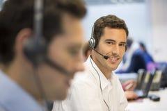 Επιχειρηματίας στο γραφείο στο τηλέφωνο με την κάσκα, που φαίνεται έκκεντρο Στοκ Εικόνες