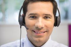 Επιχειρηματίας στο γραφείο στο τηλέφωνο με την κάσκα, που φαίνεται έκκεντρο Στοκ φωτογραφίες με δικαίωμα ελεύθερης χρήσης