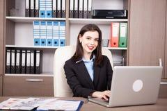Επιχειρηματίας στο γραφείο της που λειτουργεί στο lap-top Στοκ Εικόνες
