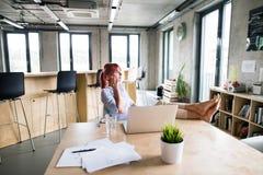 Επιχειρηματίας στο γραφείο της, που μιλά στο τηλέφωνο Στοκ Φωτογραφία