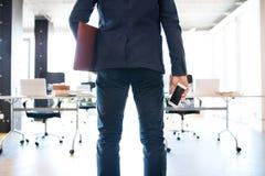 Επιχειρηματίας στο γραφείο του με το smartphone και το χαρτοφύλακα Στοκ εικόνες με δικαίωμα ελεύθερης χρήσης