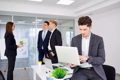 Επιχειρηματίας στο γραφείο του που λειτουργεί σε ένα lap-top στο Bu υποβάθρου Στοκ Φωτογραφίες
