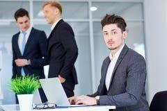 Επιχειρηματίας στο γραφείο του που λειτουργεί σε ένα lap-top στο Bu υποβάθρου Στοκ Εικόνα
