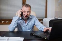 Επιχειρηματίας στο γραφείο του που μιλά στο τηλέφωνο συναισθηματικά Στοκ φωτογραφία με δικαίωμα ελεύθερης χρήσης