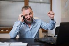 Επιχειρηματίας στο γραφείο του που μιλά στο τηλέφωνο συναισθηματικά Στοκ Εικόνες