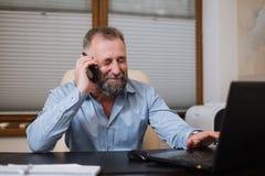 Επιχειρηματίας στο γραφείο του που μιλά στο τηλέφωνο συναισθηματικά Στοκ Φωτογραφίες