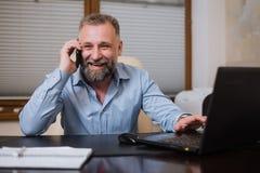 Επιχειρηματίας στο γραφείο του που μιλά στο τηλέφωνο συναισθηματικά Στοκ εικόνα με δικαίωμα ελεύθερης χρήσης