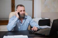 Επιχειρηματίας στο γραφείο του που μιλά στο τηλέφωνο συναισθηματικά Στοκ Φωτογραφία