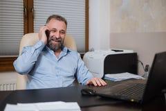 Επιχειρηματίας στο γραφείο του που μιλά στο τηλέφωνο συναισθηματικά Στοκ φωτογραφίες με δικαίωμα ελεύθερης χρήσης