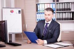 Επιχειρηματίας στο γραφείο του στο γραφείο που εξετάζει έναν φάκελλο Στοκ Εικόνα