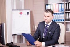Επιχειρηματίας στο γραφείο του στο γραφείο που εξετάζει έναν φάκελλο Στοκ Φωτογραφίες