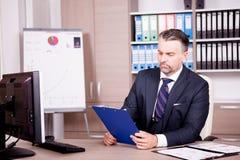 Επιχειρηματίας στο γραφείο του στο γραφείο που εξετάζει έναν φάκελλο Στοκ εικόνα με δικαίωμα ελεύθερης χρήσης