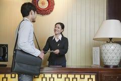 Επιχειρηματίας στο γραφείο υποδοχής του ξενοδοχείου, χαμογελώντας ρεσεψιονίστ στοκ εικόνα
