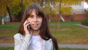 Επιχειρηματίας στο επιχειρησιακό κοστούμι που μιλά στο smartphone και το χαμόγελο Το κορίτσι επικοινωνεί τηλεφωνικώς Κινηματογράφ απόθεμα βίντεο