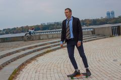 Επιχειρηματίας στο επιχειρησιακό κοστούμι στην πόλη με skateboard στοκ εικόνες
