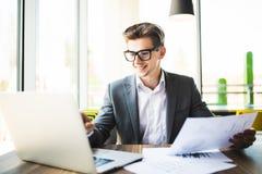 Επιχειρηματίας στο κοστούμι και γυαλιά που λειτουργούν με το lap-top και έγγραφα στην αρχή Στοκ εικόνα με δικαίωμα ελεύθερης χρήσης