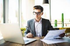 Επιχειρηματίας στο κοστούμι και γυαλιά που λειτουργούν με το lap-top και έγγραφα στην αρχή Στοκ Εικόνα