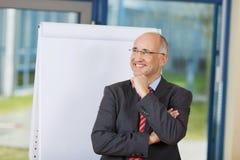Επιχειρηματίας στο κοστούμι που κοιτάζει μακριά στεμένος ενάντια σε Flipchar Στοκ εικόνες με δικαίωμα ελεύθερης χρήσης