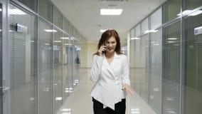 Επιχειρηματίας στο κοστούμι που περπατά και που μιλά στο κινητό τηλέφωνο στο διάδρομο του γραφείου απόθεμα βίντεο