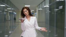 Επιχειρηματίας στο κοστούμι που περπατά και που μιλά στο κινητό τηλέφωνο στο διάδρομο του γραφείου φιλμ μικρού μήκους