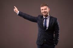 Επιχειρηματίας στο κοστούμι που χαμογελά και που παρουσιάζει δάχτυλό του Στοκ Εικόνα