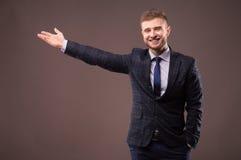 Επιχειρηματίας στο κοστούμι που χαμογελά και που παρουσιάζει χέρι Στοκ εικόνες με δικαίωμα ελεύθερης χρήσης