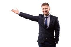 Επιχειρηματίας στο κοστούμι που χαμογελά και που παρουσιάζει χέρι Στοκ Φωτογραφίες