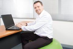 επιχειρηματίας στο λειτουργώντας lap-top σφαιρών σταθερότητας Στοκ Φωτογραφία