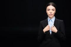 Επιχειρηματίας στο μαύρο κοστούμι που εξετάζει τη κάμερα απομονωμένη στο Μαύρο Στοκ Εικόνα